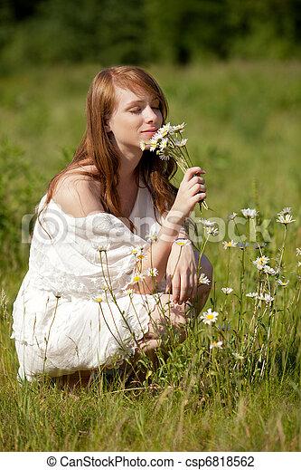 Eine junge, hübsche Frau pflückt Margeriten und andere Wildblumen/A young, beautiful lady picks flowers on a summer meadow  - csp6818562