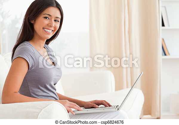close up of a smiling woman sitting crossleged on sofa working with notebook in livingroom - csp6824676