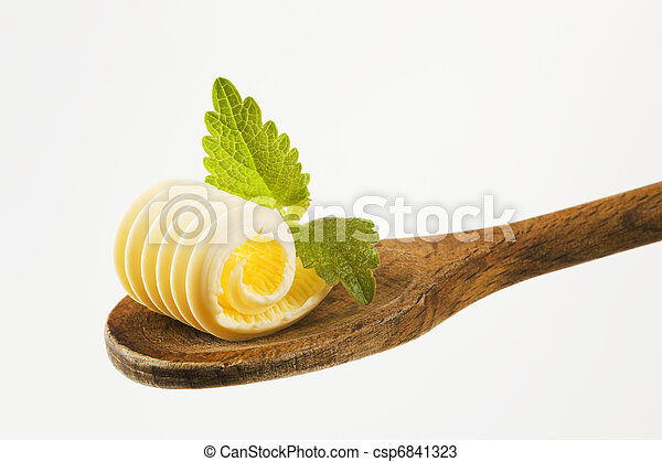 Butter curl on a wooden spoon  - csp6841323