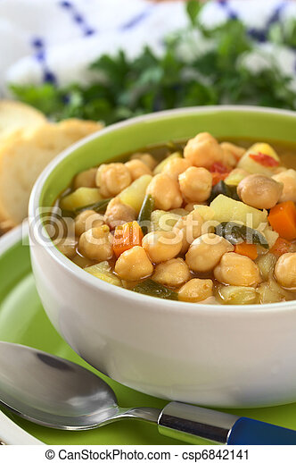 Vegetarian chickpea soup with carrots, potatoes, onions and leek (Selective Focus, Focus on the row of chickpeas in the front of the soup) - csp6842141