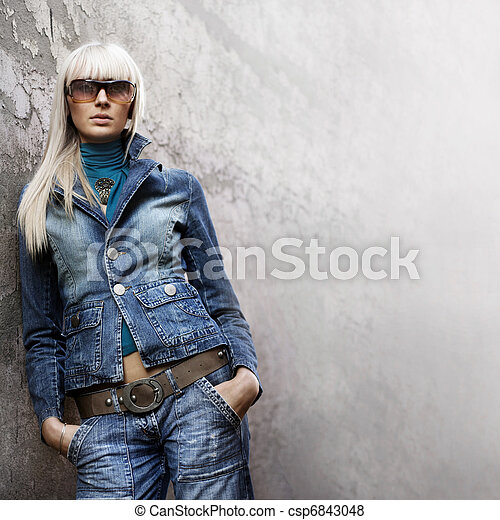 portrait of stylish casual girl with sunglasses in front of a wall - csp6843048