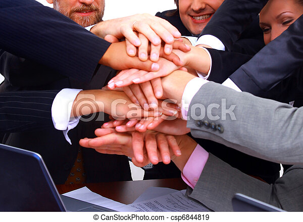 group of business people making a pile of hands in a light and modern office environment - csp6844819