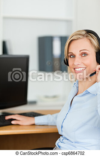 Close up of a smiling blonde businesswoman with headset working with computer looking into camera in her office - csp6864702