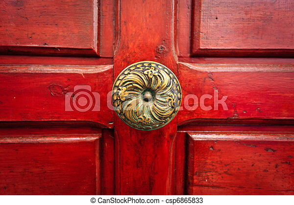 Brass doorknob and red door