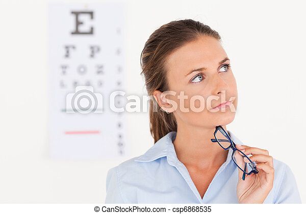 Thinking eye specialist holding glasses - csp6868535