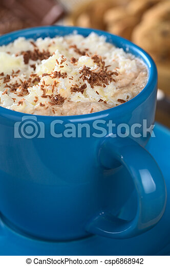 Hot chocolate with whipped cream and chocolate shavings in blue cup with cookies and chocolate in the back (Selective Focus, Focus on the top of the cream) - csp6868942