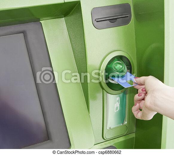 Female inserts a plastic card in the ATM - csp6880662