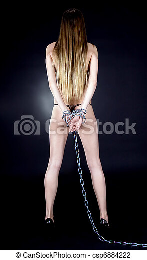 Sexy brunette with nude back in chains over black background - csp6884222