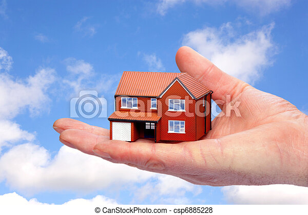 Hand holding a model home against sky background. - csp6885228