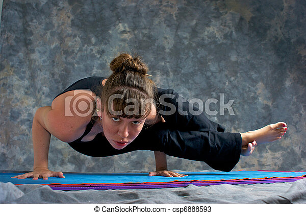 A brown haired caucasian woman is doing yoga exercise, Astavakrasana Pose or Ancient Sage Cursed with Crooked Limbs  posture  on yoga mat in studio with mottled background.