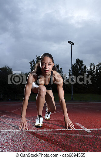 Female athlete in starting position on track - csp6894555