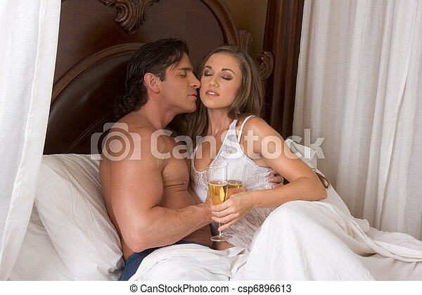Loving young sensual couple with Champagne in bed - csp6896613