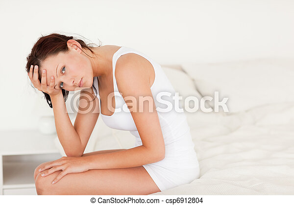 Ill-feeling woman sitting on her bed - csp6912804