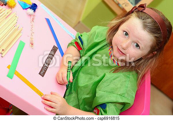 happy smiling kid drawing at home or school kindergarden or kindergarten - csp6916815