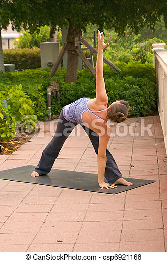 an athletic brown haired woman is doing yoga exercise triangle pose outside on a sidewalk in public on an overcast morning. - csp6921168