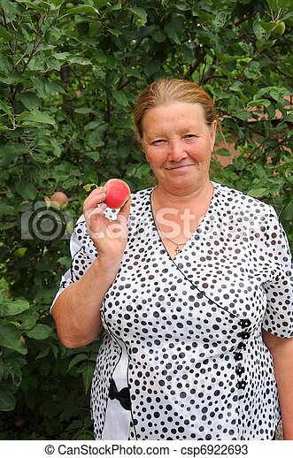 Pensioner in the garden with a red apple in his hand - csp6922693