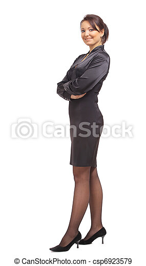 Full length portrait of a beautiful business woman standing with hands folded over white background  - csp6923579