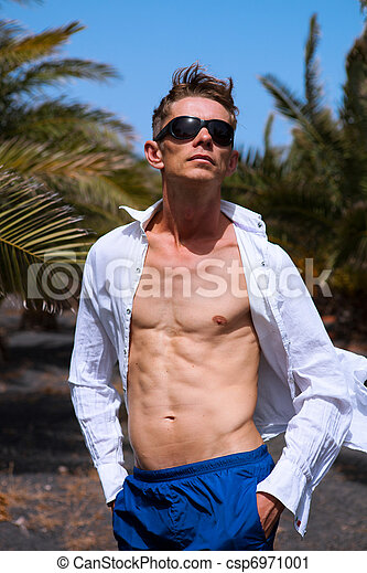 Young sexy man in sunglasses among palm trees on a windy day