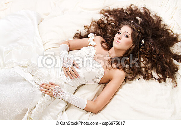 Bride with curly long hair lying over white. High angle view. Fashion wedding shoot. - csp6975017