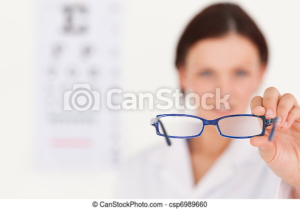 Blurred optician showing glasses - csp6989660
