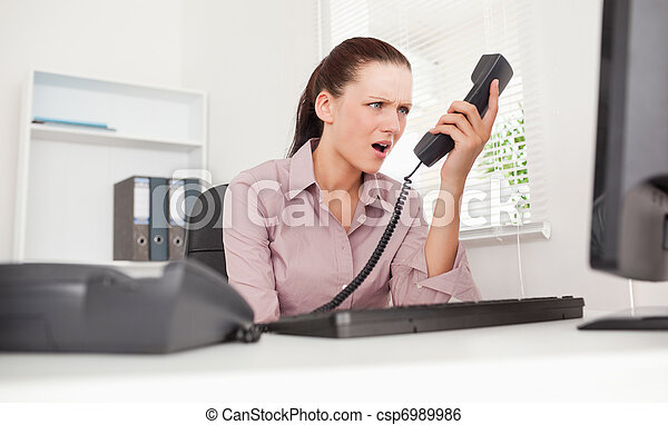 Depressed businesswoman shouting at telephone - csp6989986