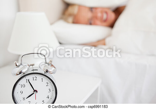 Woman hiding her head in a pillow while the alarm clock is ringing in her bedroom - csp6991183
