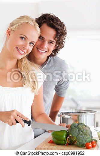 Portrait of a beautiful couple cooking - csp6991952