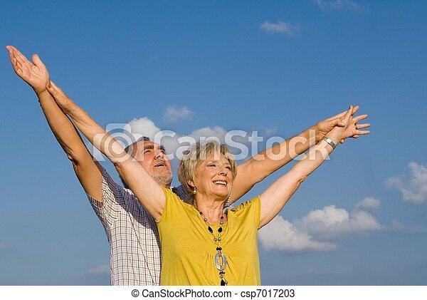 healthy active christian senior couple arms raised in praise - csp7017203