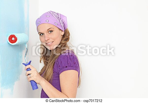 woman painting home nursery wall with roller paint - csp7017212
