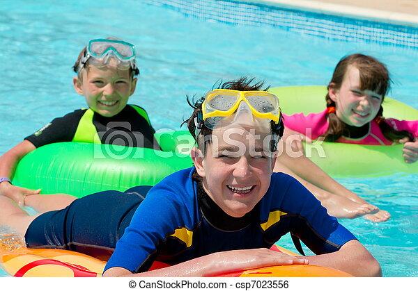 Kids playing in swimming pool  - csp7023556