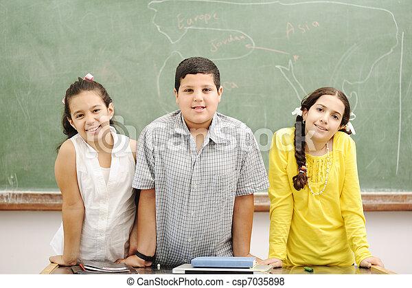 Education activities in classroom at school, happy children learning - csp7035898