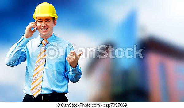 Young architect wearing a protective helmet standing on the building background - csp7037669