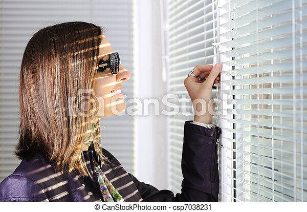 Young brunette woman in the sunlight looking through  jalousie on window - csp7038231