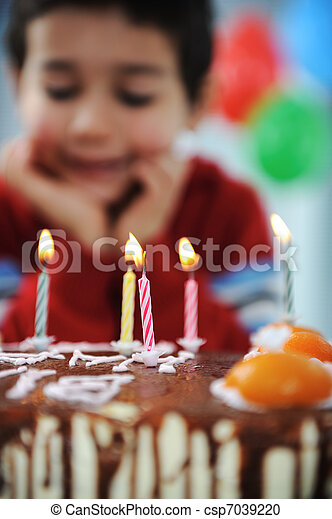 Boy blowing candles on cake, happy birthday party - csp7039220