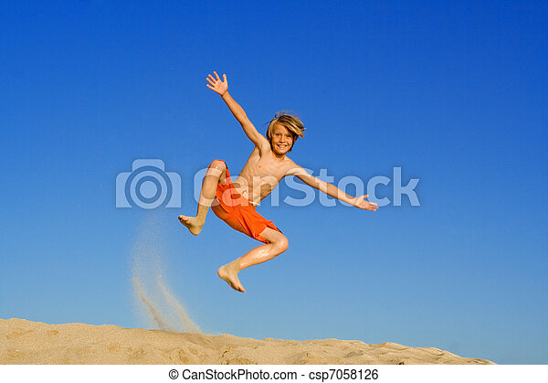 child jumping and playing on beach summer vacation or holiday - csp7058126