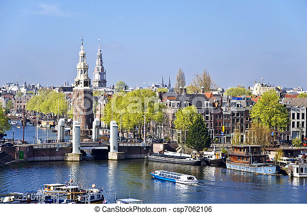 Classical Amsterdam view. Boat floats on the channel on the background of bridge. Urban scene. - csp7062106