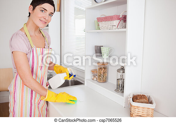 Beautiful woman cleaning a cupboard - csp7065526