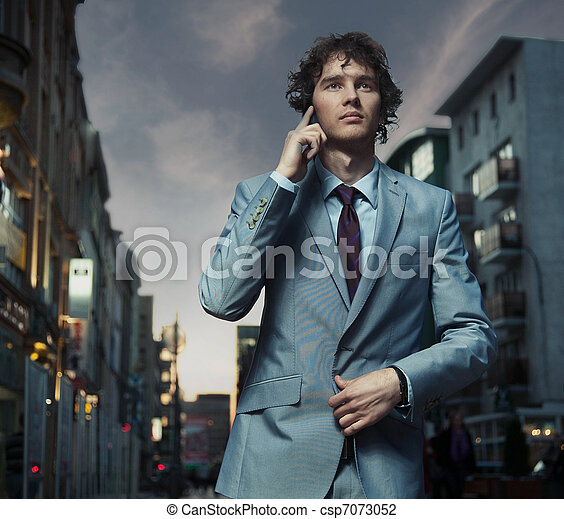 Elegant man posing on a city street - csp7073052