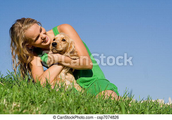 young woman or teen girl playing with pet cocker dog - csp7074826
