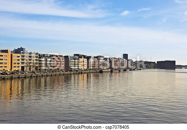 Modern architecture in Amsterdam. Island of Borneo. Modern housing is reflected in the water against the blue sky.