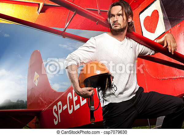 Young handsome man posing next to aeroplane - csp7079630
