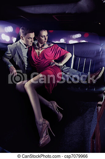 Handsome couple hugging in a luxury limousine - csp7079966