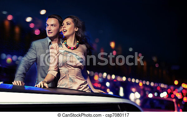 Elegant couple traveling a limousine at night - csp7080117