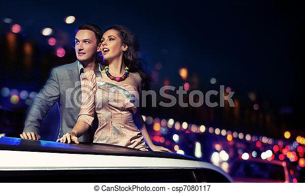 Elegant couple traveling a limousine at night - csp7080117