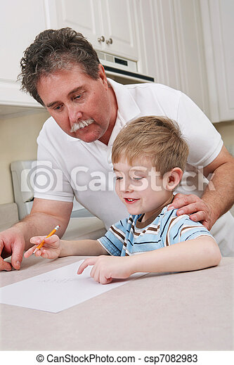 Middle aged father helping young son with homework - csp7082983