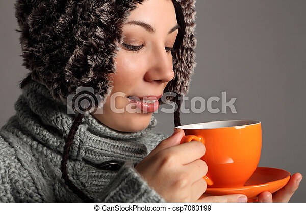 Young woman in warm winter hat drinking hot tea - csp7083199
