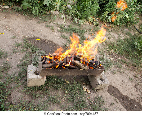 fire in a brazier on the background of green forest - csp7094457