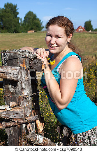 One young woman near village fence - csp7098540