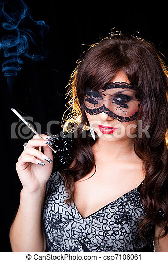portrait of attractive young brunette girl with long dark ringlets and fine art manicure wearing lacy mask on her eyes holding graceful silver mouthpiece and smoking thin ladies' cigaret on black bac - csp7106061
