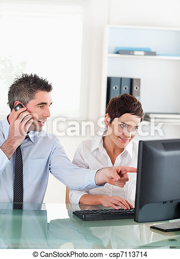 Portrait of a man showing something to his coworker on a computer in an office - csp7113714